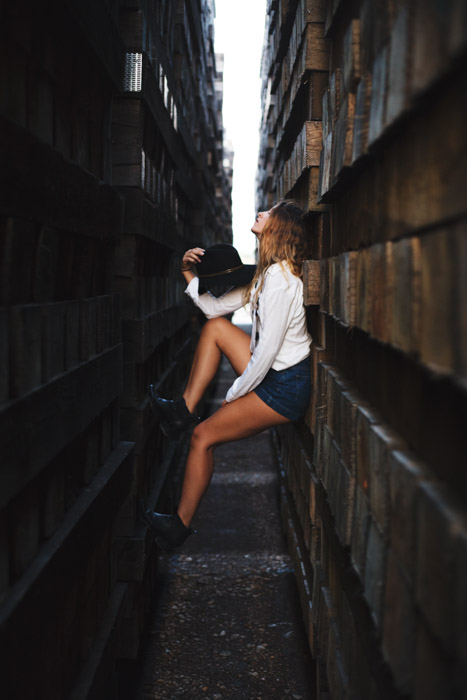 Cool editorial style portrait of a girl standing between two walls, people posing in photographs