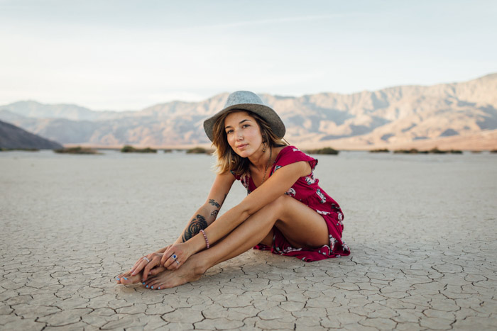 Bright portrait of a girl sitting on a desert ground, posing people in photographs