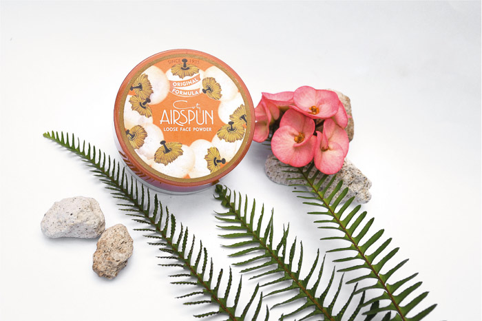 A product photography styling example of a cosmetic product arranged with flowers and stones on white background