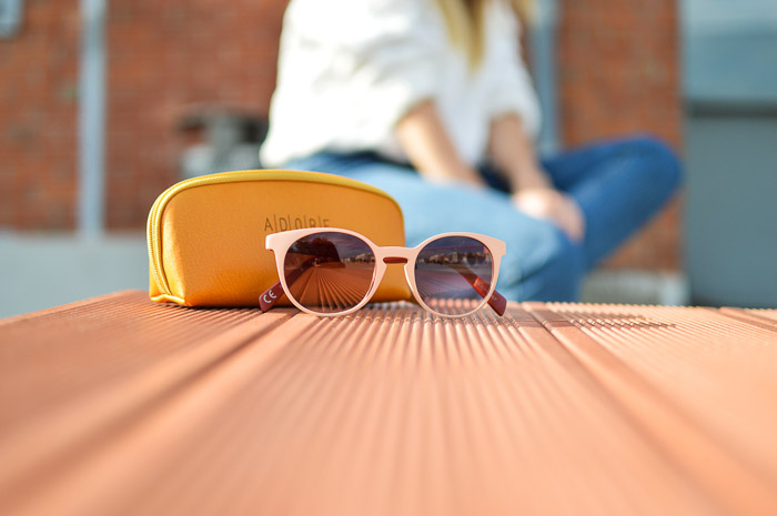 A product photography styling example of sunglasses and case on a table, with a blurry figure sitting in the background
