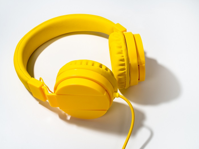 A product photography styling example of a pair of yellow headphones on white background