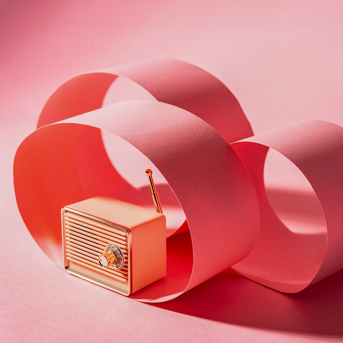 A product photography styling example of avintage radio surrounded by pink paper on pink background
