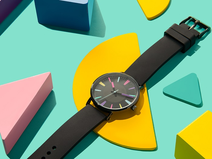 A product photography styling example of a digital watch displayed on bright shapes