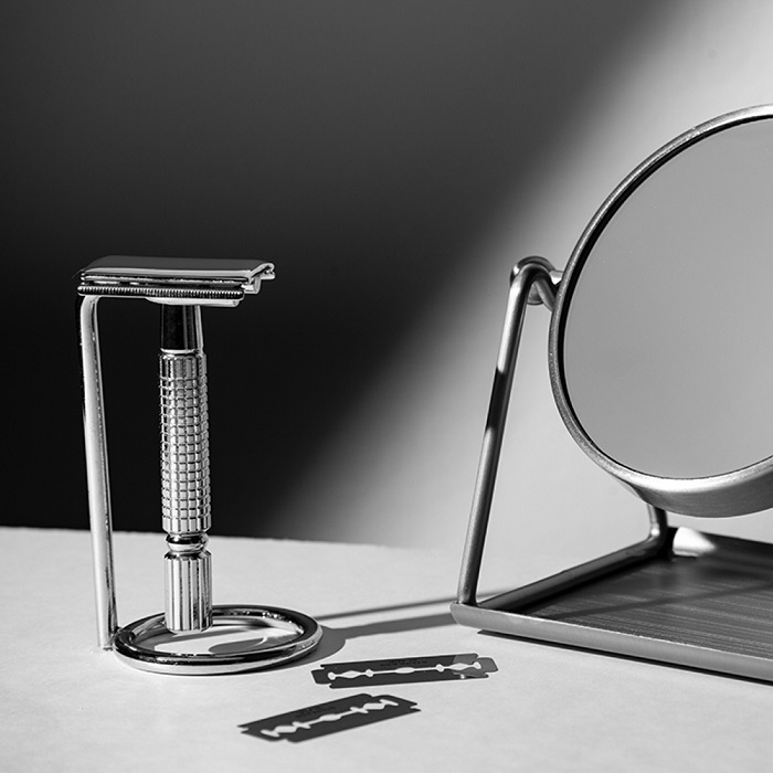 Product styling shot of a razor beside a mirror