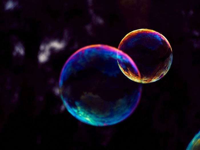 macro photo of two colorful soap bubbles