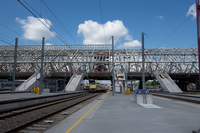 Photo of a train pulling into a railway station on a day with blue skies and clouds