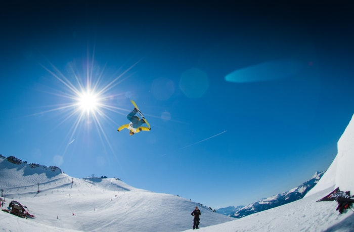 Snowboarder int the air above snowy mountains