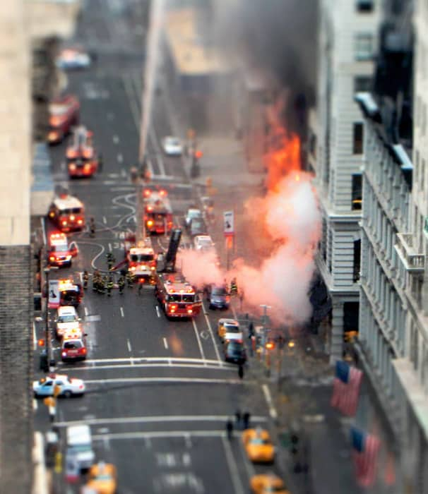 Overhead shot of a fire in an urban setting. Fire engines and fireman and many cars line the streets. The use of tilt shift photography makes the scene look like its made from toys.