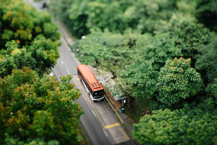 A tilt shift photo of a bus parked on a road in a beautiful countryside area surrounded by trees