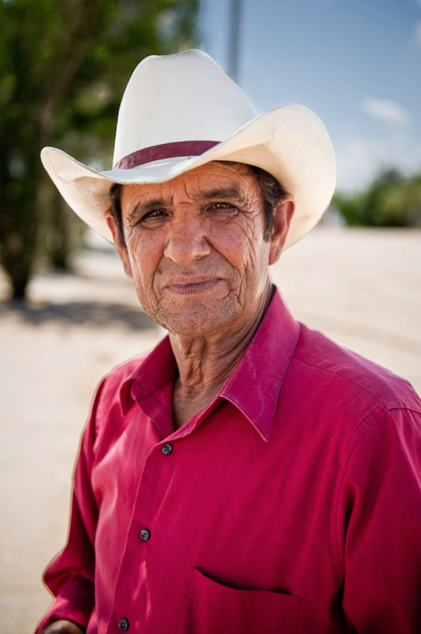 A travel photo of a man in a cowboy hat and pink shirt - tipping for photos of people