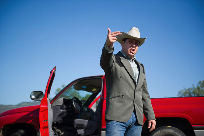 A man in a cowboy hat standing in front of a red car and making a hand gesture - tipping for photos of people