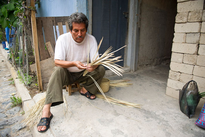 A travel photo of a man sitting outside a stone building, holding straw.