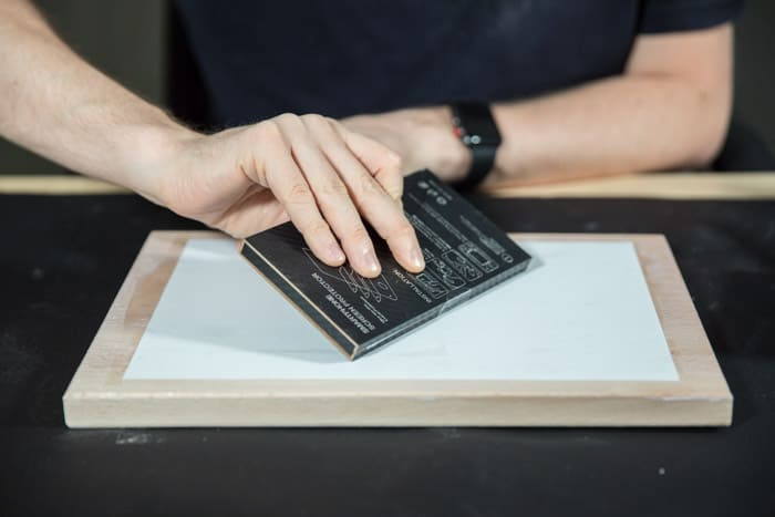 A man preparing a wooden board to transfer laser print to wood