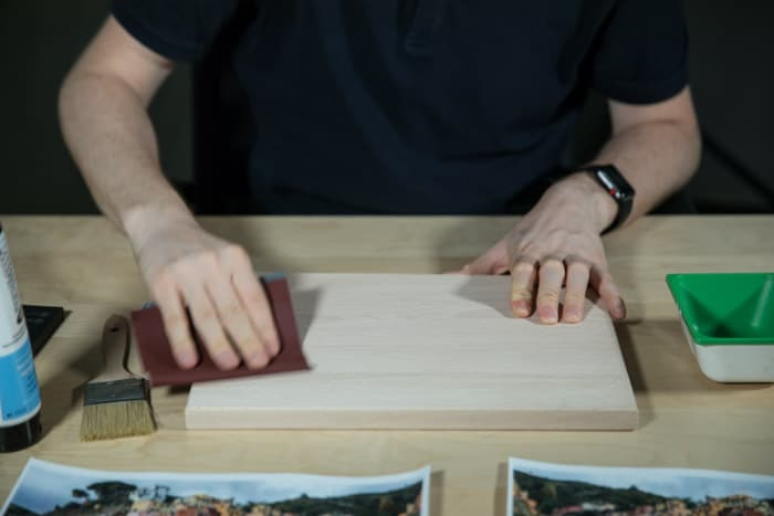 A man sits at a wooden table, sanding a wooden board to prepare the surface for to transfer photo to wood