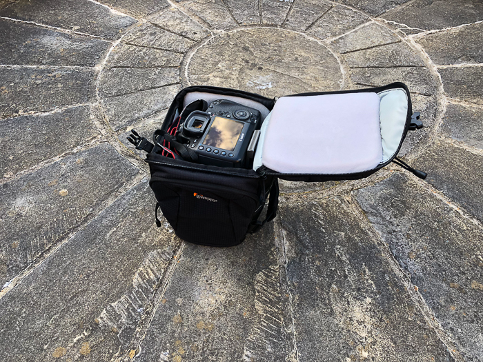 a toploader DSLR camera bag on stone ground