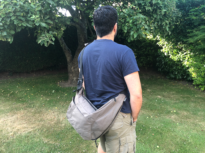 Photo of a man carrying a sling camera bag