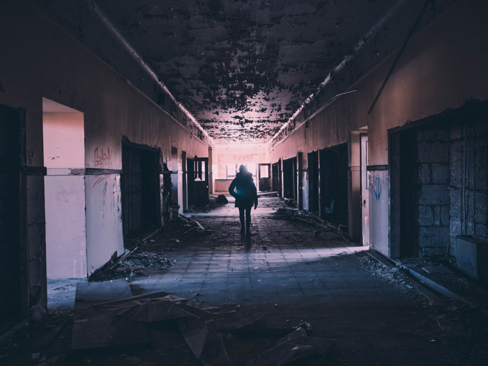A person walking through the corridor of an abandoned building during an urban exploration trip