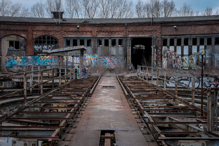 the tracks and exterior of an abandoned train station