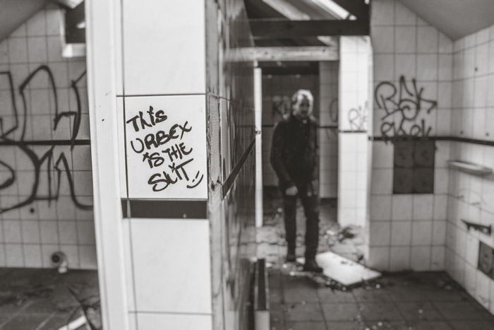 A black and white photo of a man walking an abandoned building during an urban exploration trip