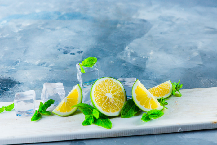 Set up for water splash photography with acrylic ice cubes, limes on blue background