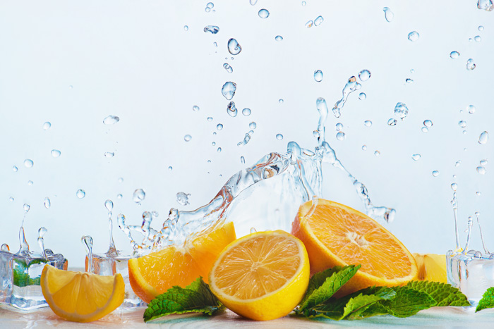 a creative food photography set up with oranges and water splashes on white background