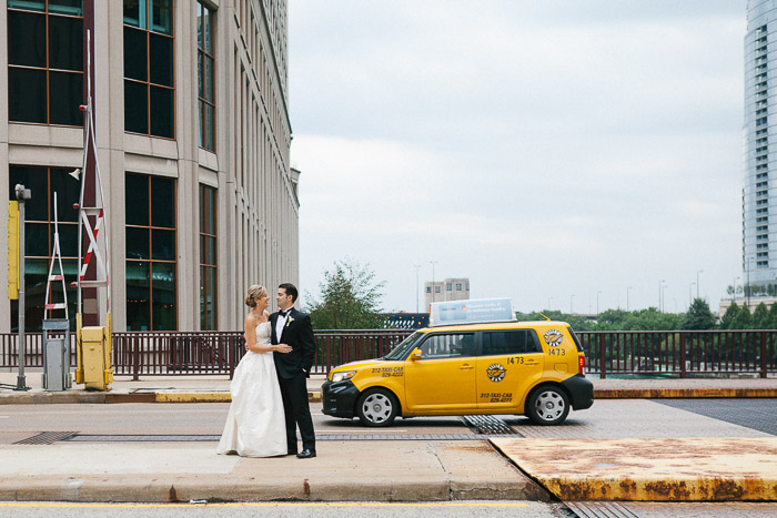 a newly wedding couple pose on the street in front of a yellow taxi