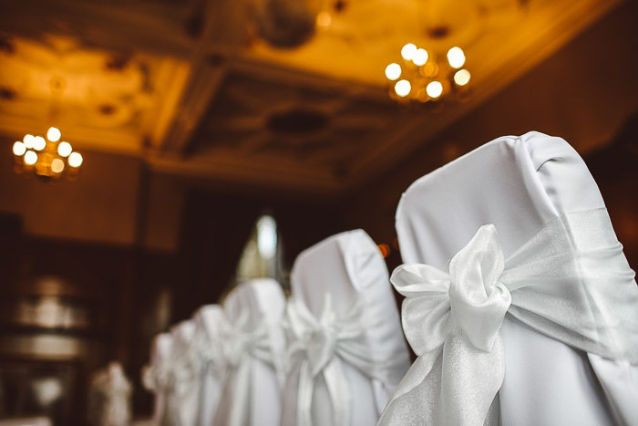 A row of chairs decorated for a wedding ceremony. Wedding photography gear