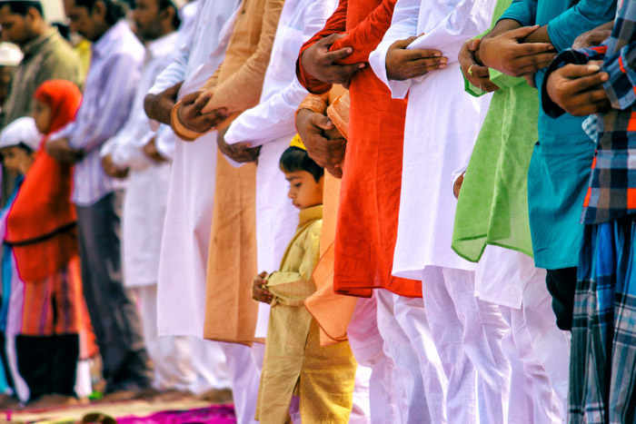 A crowd of people with arms folded in prayer, focused on a little boy