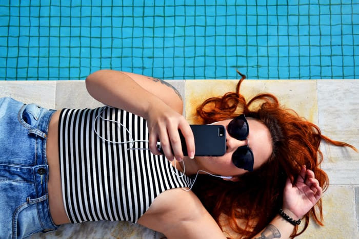 Overhead shot of a girl sunbathing by a swimming pool while editing photos on her smartphone