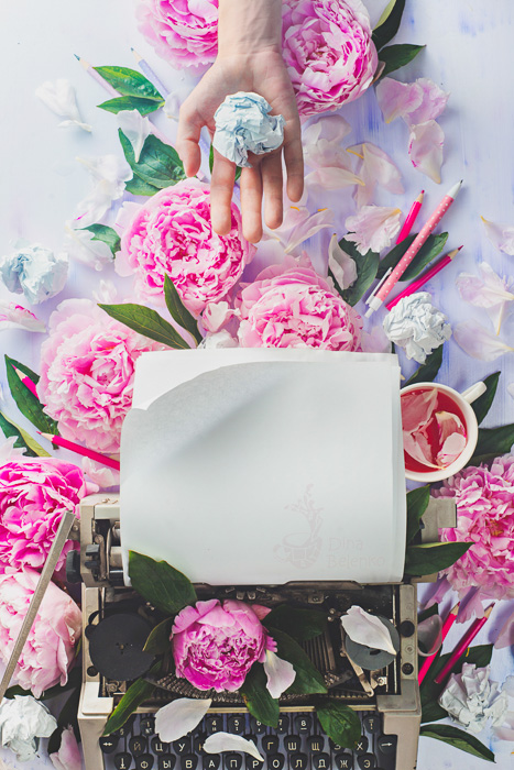 A bright and airy still life with a typewriter, pink roses and a hand holding a crumpled ball of paper