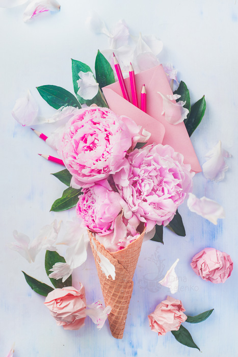 A bright and airy still life with an ice-cream cone filled with roses on a light background