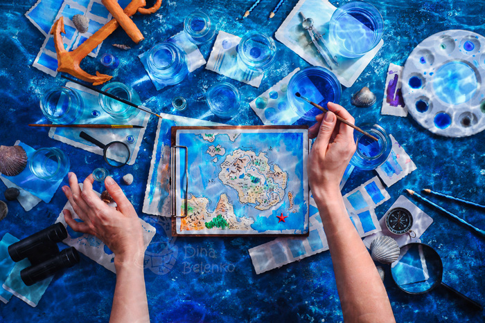 Flat lay photography of hands painting a small map underwater
