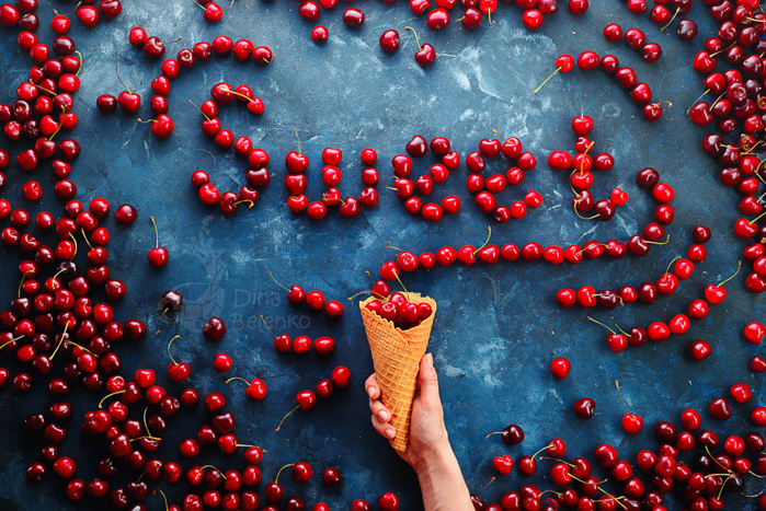 A fun food photo of cherries spelling the word 'sweet' on blue surface with a hand holding an ice-cream cone underneath