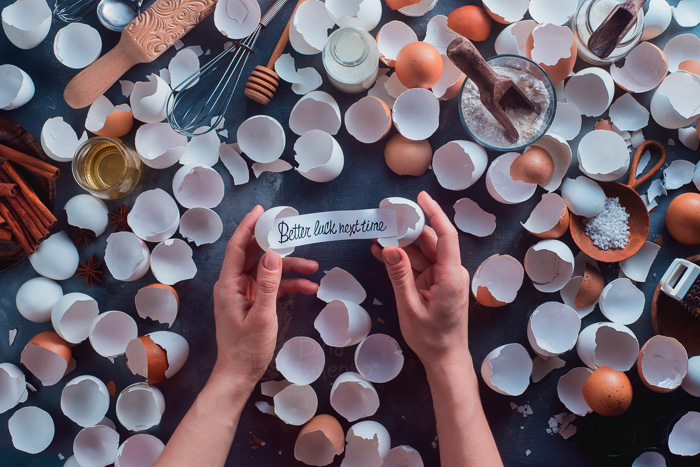 A food photography themed still life with egg shells, cooking utensils and hands holding a note saying 'better luck next time'