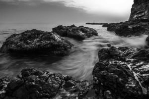 A black and white fine art photography shot of a rocky beach, with a soft misty effect of the water around the rocks and cliffs