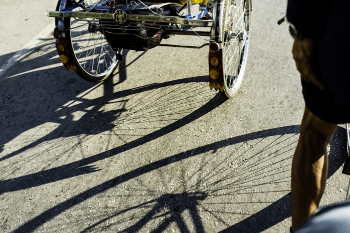 An interesting street photography composition of the shadows of Saamlar bike wheels cast on a road