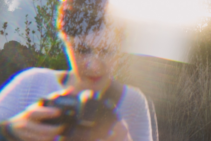 A woman in a stripy top holding a camera, overlayed with dreamy prism photo effect