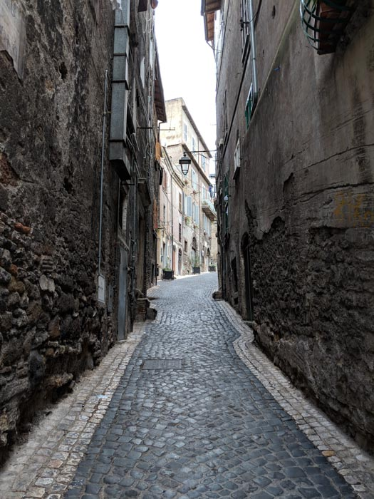 An architecture photo of cobblestones streets and brick buildings taken through an alleyway