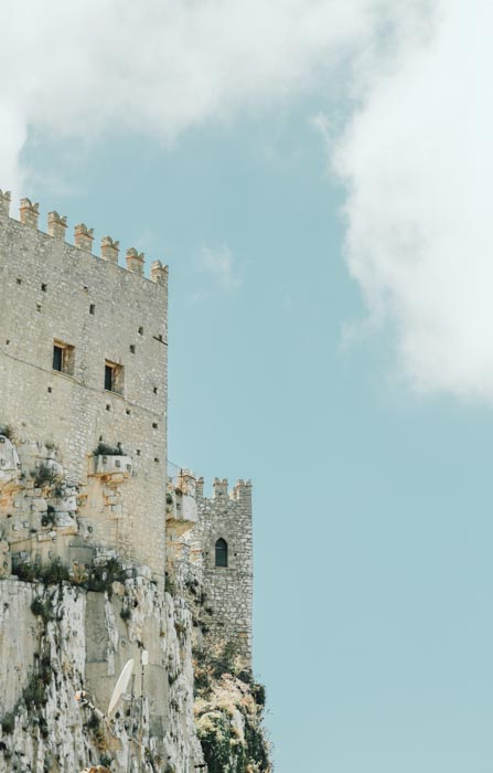 A photo of the exterior of a stone castle against a cloudy blue sky