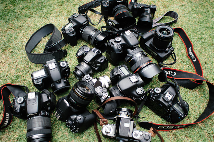 A overhead shot of 13 different types and brands of camera on grass - best camera fro portraits