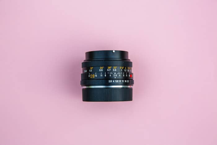 Overhead photo of a DSLR camera lens on pink background -how to create a bokeh background