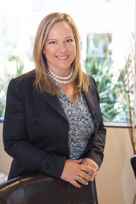 A corporate portrait of a woman in a business suit in an office setting