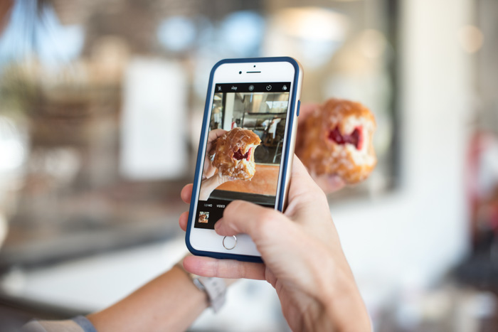close up of a person taking an iPhone photo of food
