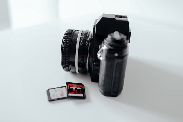 A camera with two memory cards beside it on a white background