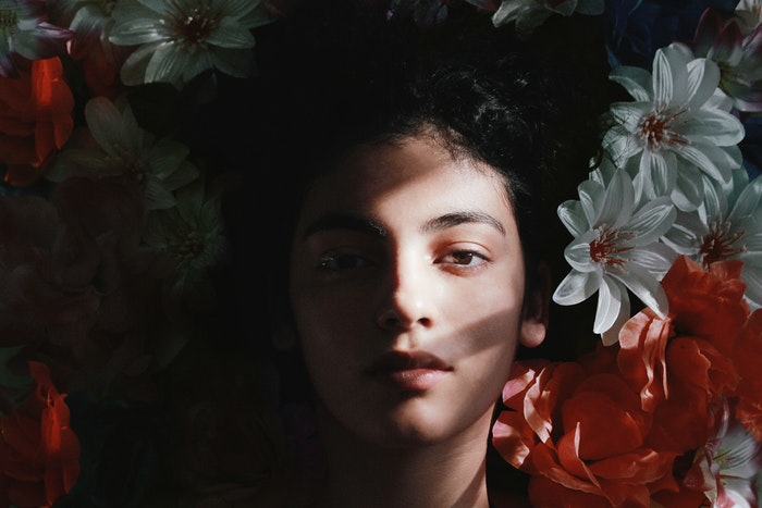 A womans face surrounded by flowers