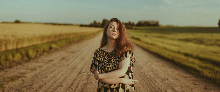 Beautiful close up portrait of a female posing on a country road shot using ambient light