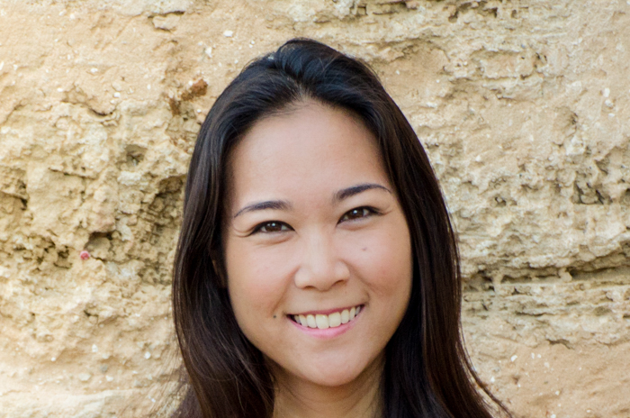 headshot of smiling asian woman in front of sandy stone wall