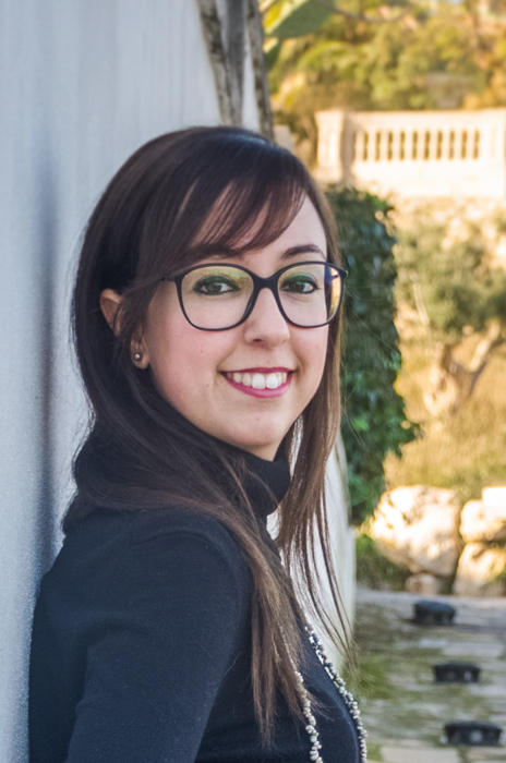 cropped portrait of brunette with eyeglasses leaning against a while wall on a sunny afternoon