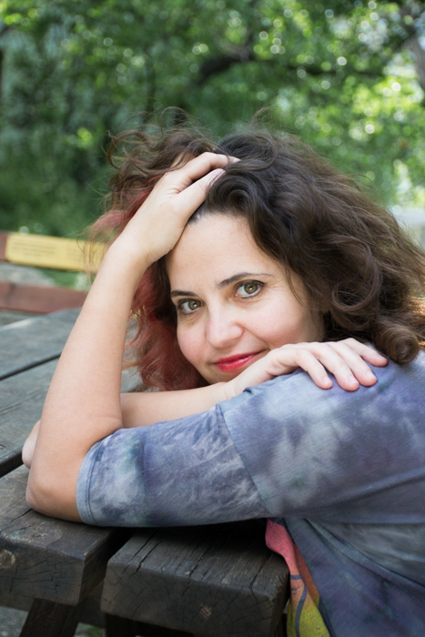 woman in grey leaning on wooden picnic table 4:3 photo