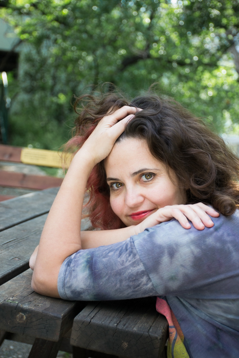 woman in grey leaning on wooden picnic table 3:2 photo